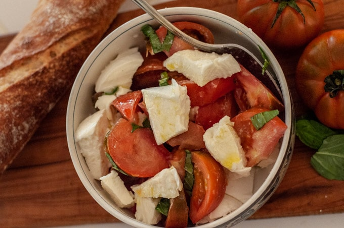 Caprese salad in a bowl with fresh bread on the side