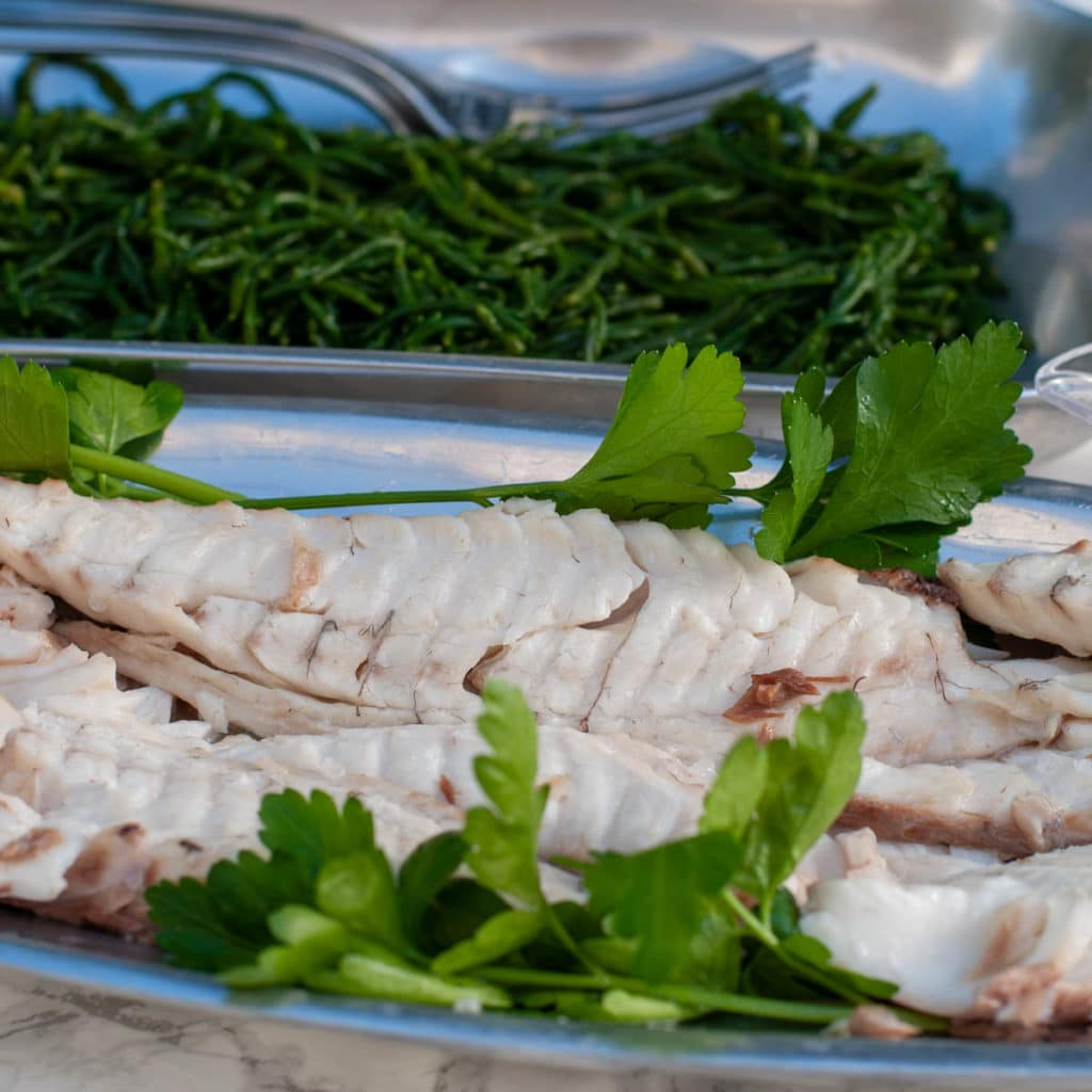 Fish baked in salt served on a serving dish separate from the vegetables