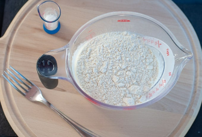 flour in a measuring cup next to salt
