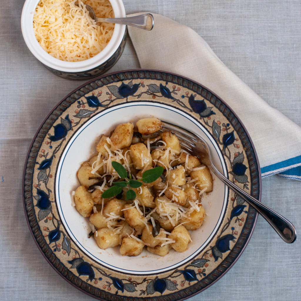 Light and Fluffy Italian Homemade Gnocchi served at the table with a bowl of Parmesan with a spoon