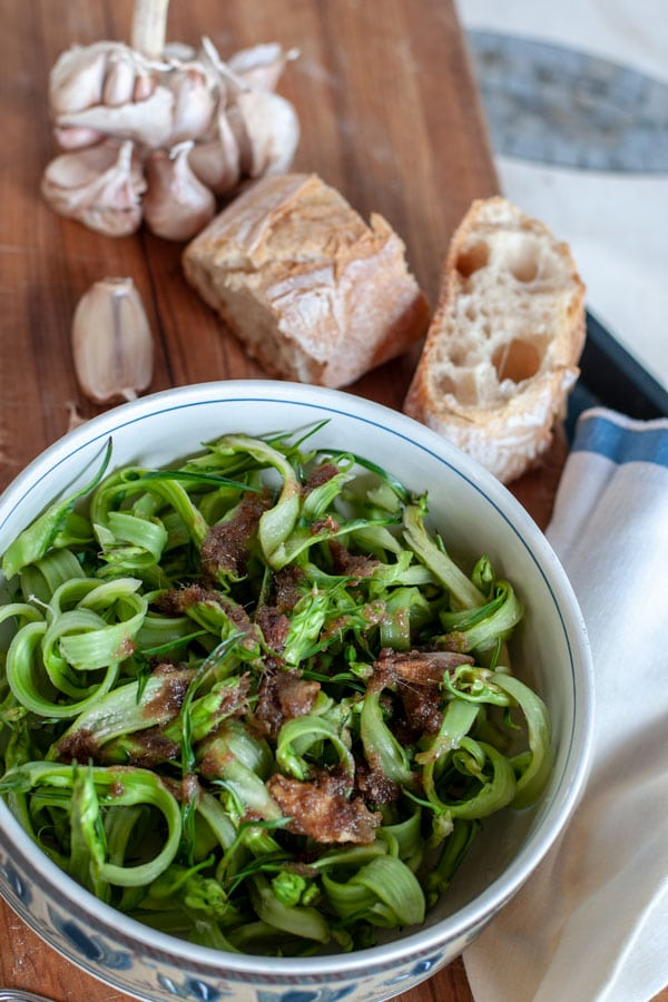 puntarelle alla romana on a plate with bread