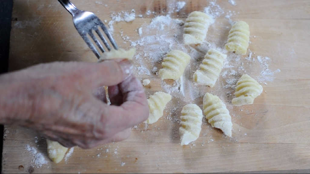 Applying a good pressure against the fork and pull down the gnocchi