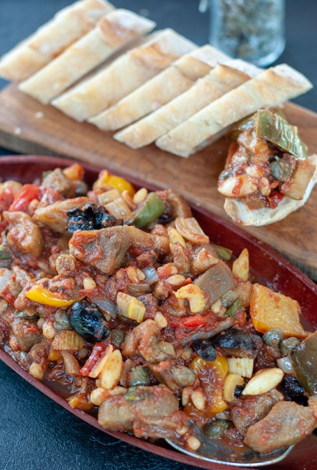 Caponata on a serving dish and in the background on a bread slices