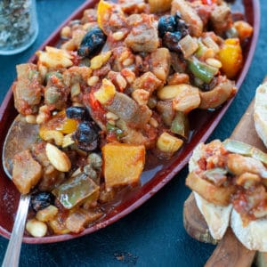 caponata on a piece of bread on a wooden board