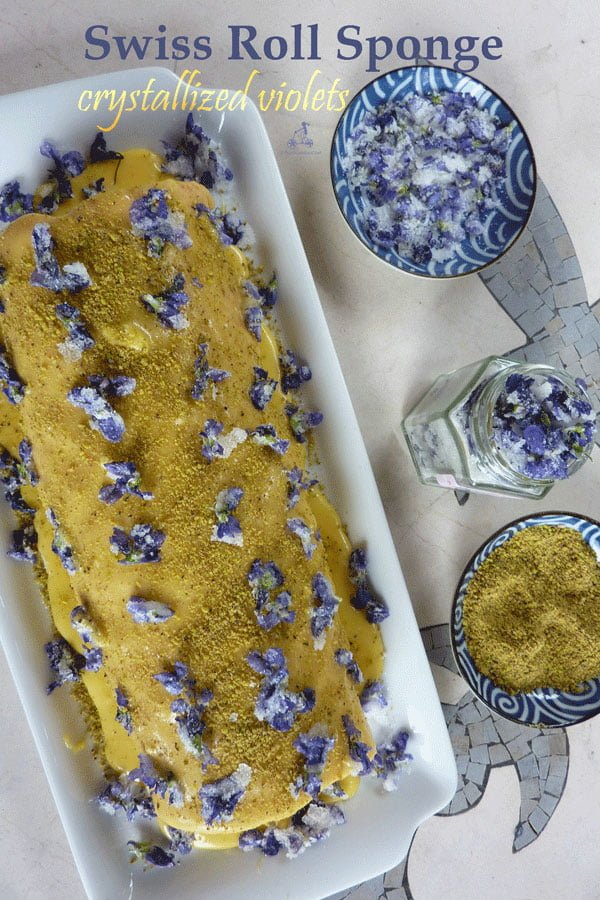 Swiss roll sponge recipe with buttercream decorated with homemade crystallized violets and pistachios. The perfect cake for a spring celebration #yourguardianchef #dessert #recipe