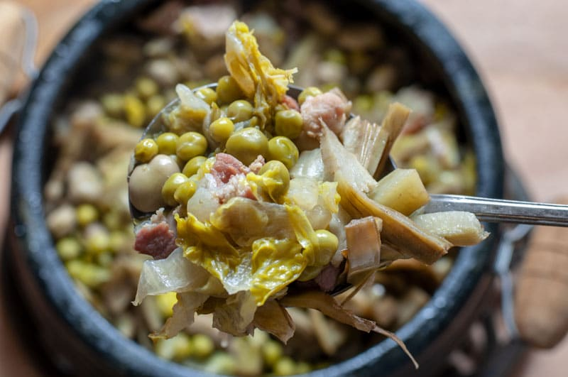 Broad beans, peas and artichokes hold on a spoon