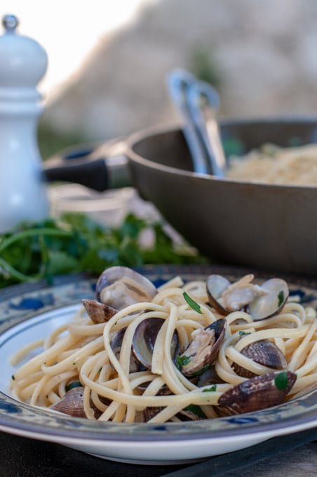 linguine with clams served on a dish with the pan on the background
