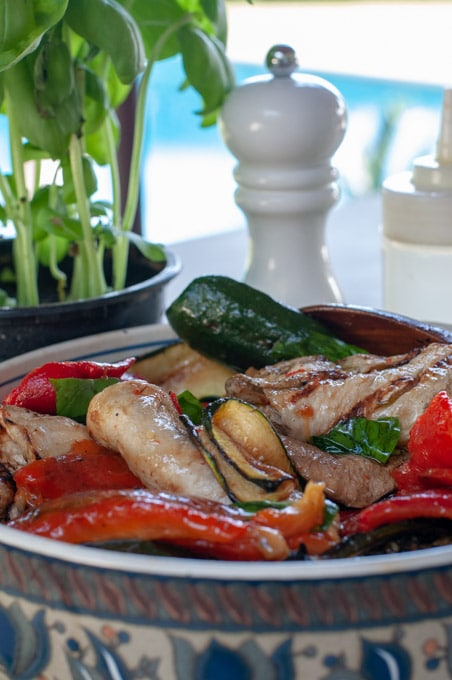 Grilled zucchini eggplants and peppers on a serving dish basil and pool in the background