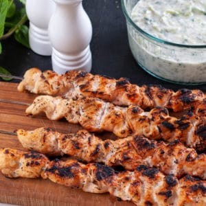 bbq chicken breast on skewers with the yogurt sauce in the back