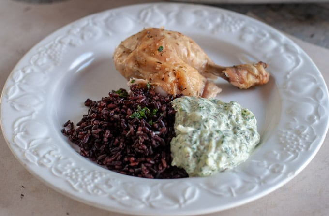 Roasted chicken with black rice and yogurt sauce on a plate