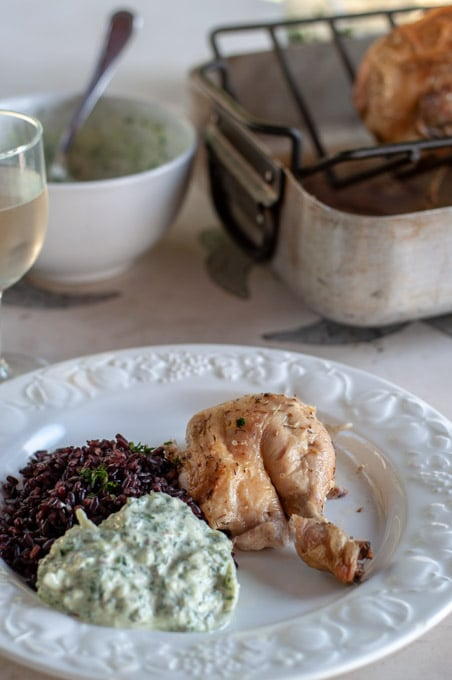 roasted chicken dinner on a plate with a glass of wine and roasting pan on the background