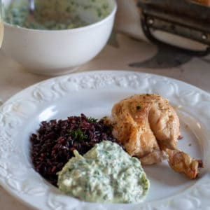 Low fat roasted chicken dinner on a plate with black rice and yogurt sauce