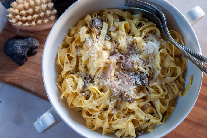 pasta with truffle on a plate with Parmigiano cheese and fresh truffle on top