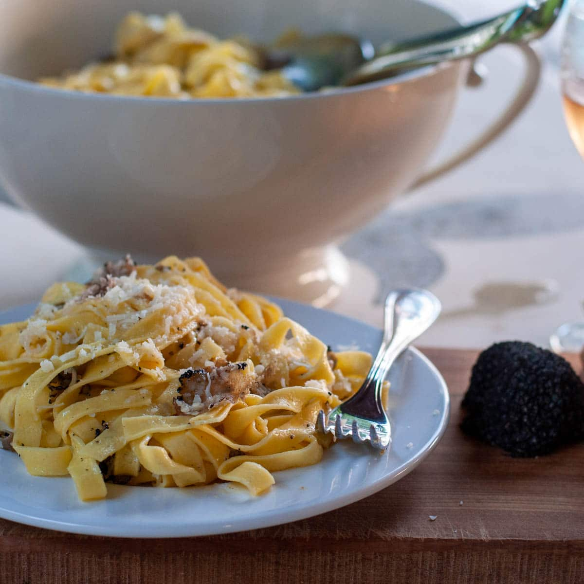 Pasta with truffle served on a plate truffle on the side and serving dish in the background
