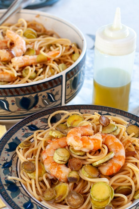 shrimp zucchini pasta on a serving plate and a dinner dish