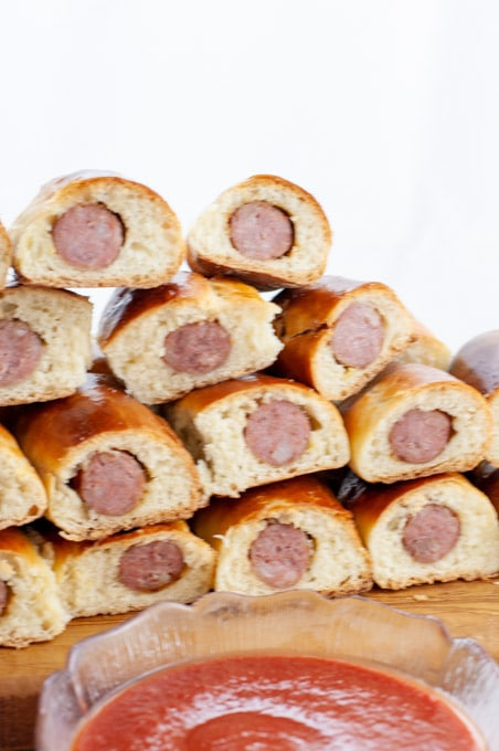 Sausage roll recipe stacked up with a sauce for dipping