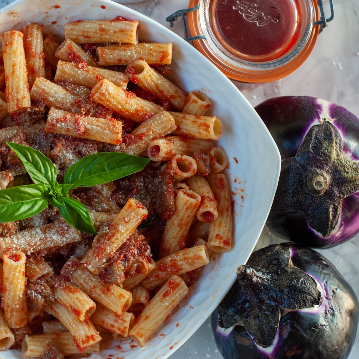 Pasta alla Norma on a serving dish with a fork taking some pasta