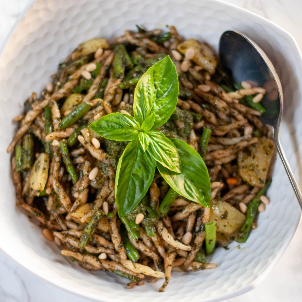 trofie with pesto Genovese on a serving plate with potatoes and green beans