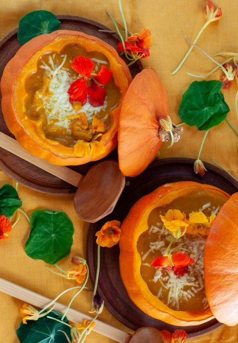 Roast Pumpkin Soup with edible flowers served in a squash bowl