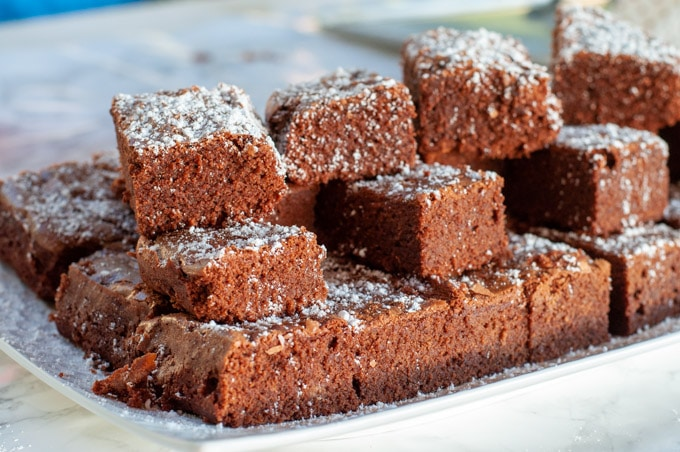 brownies on a serving plate with icing sugar