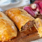 Beef sausage hand pies on a cutting board one pie cut open
