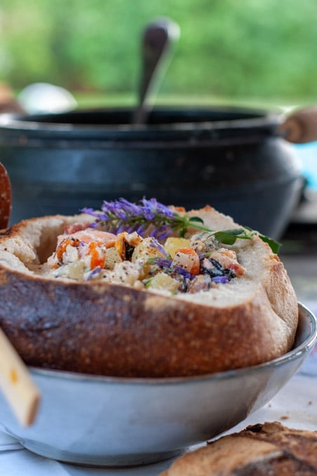 Seafood chowder served in a bread bowl decorated with Agastache