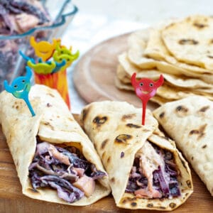Healthy chicken wraps on a wooden cutting board with some joyful sticks
