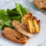 Braked breaded chicken breast served on a plate with salad and potatoes