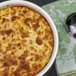 Baked tortellini souffle in the baking dish with a spoon to serve