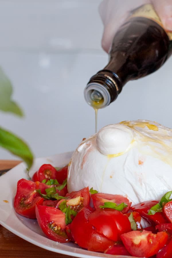 Oil pouring over a zizzona caprese salad