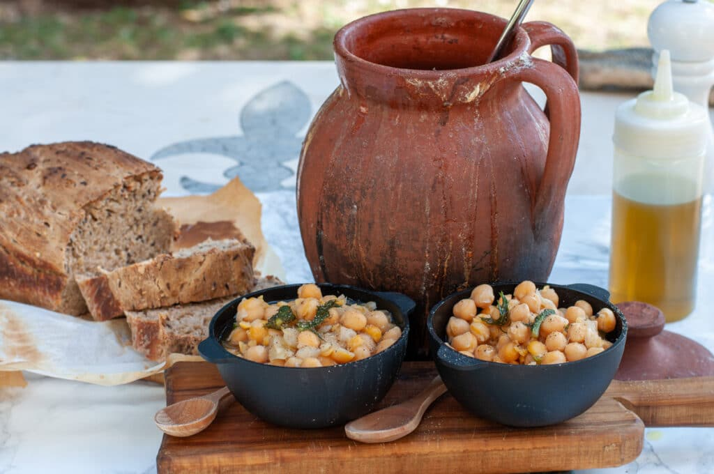 chickpeas on serving bowls with clay cooker in the back