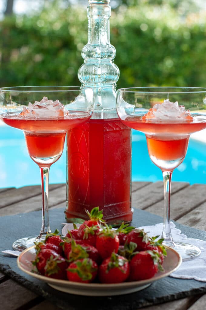 homemade strawberry liqueur in a bottle and 2 glasses served with fresh strawberries