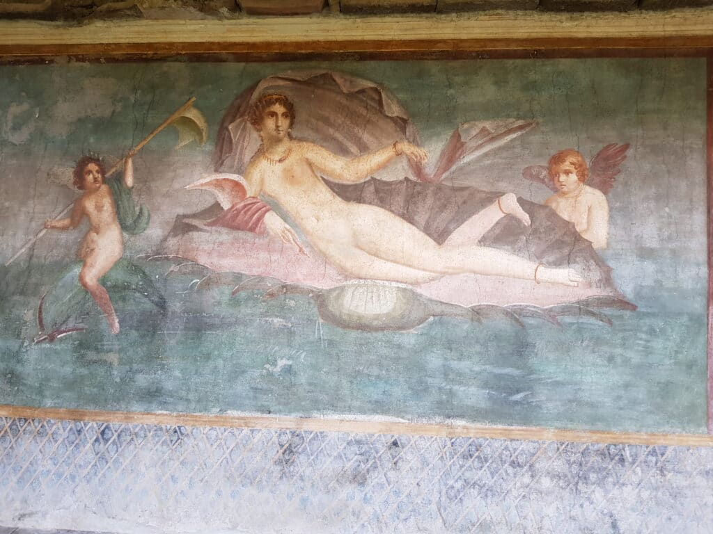 Pompeii fresco showing a lady laying on a shell over the sea and two angles on the side