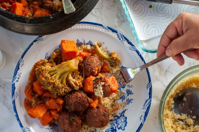 meatballs and vegetables on a fork plate with a serving behind