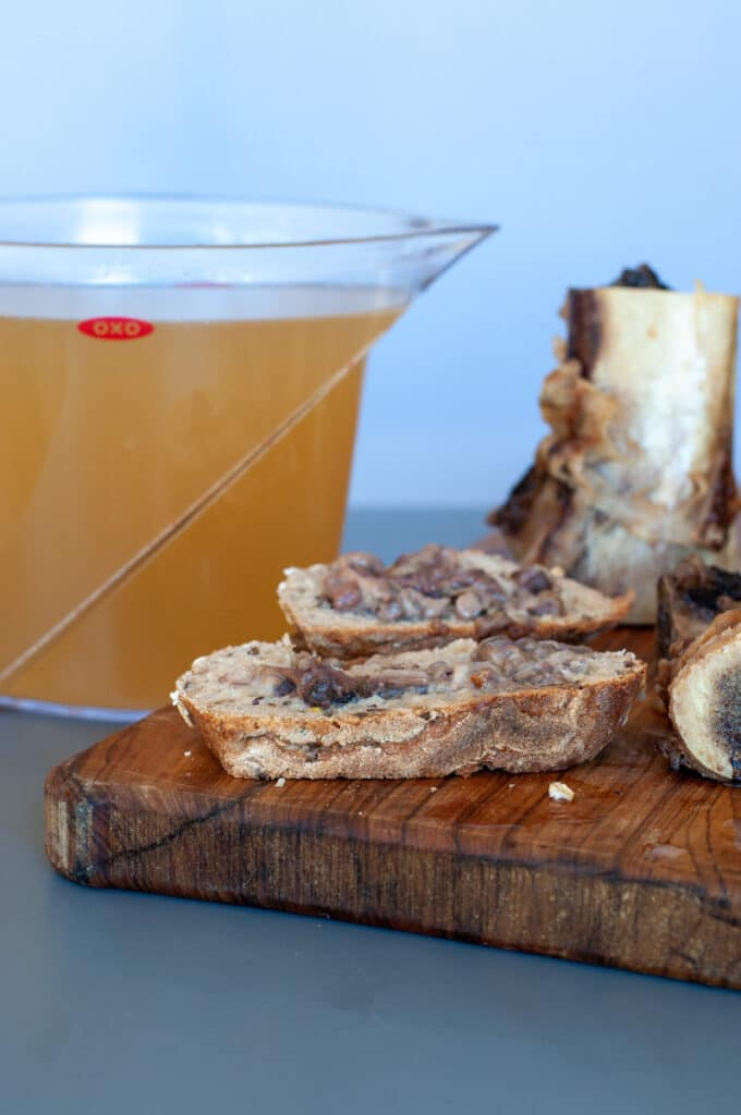 brown stock with bone marrow on the side over slices of bread