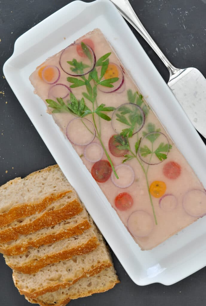 Ham hock terrine decorated with herbs and served with bread