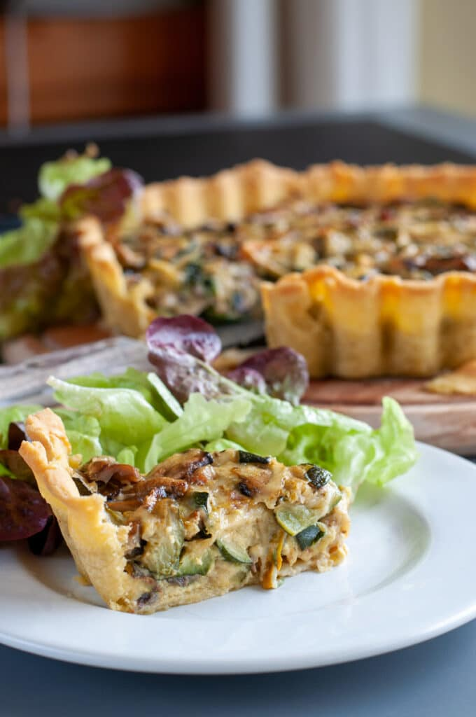 a slice of zucchini mushroom quiche served on a plate with salad