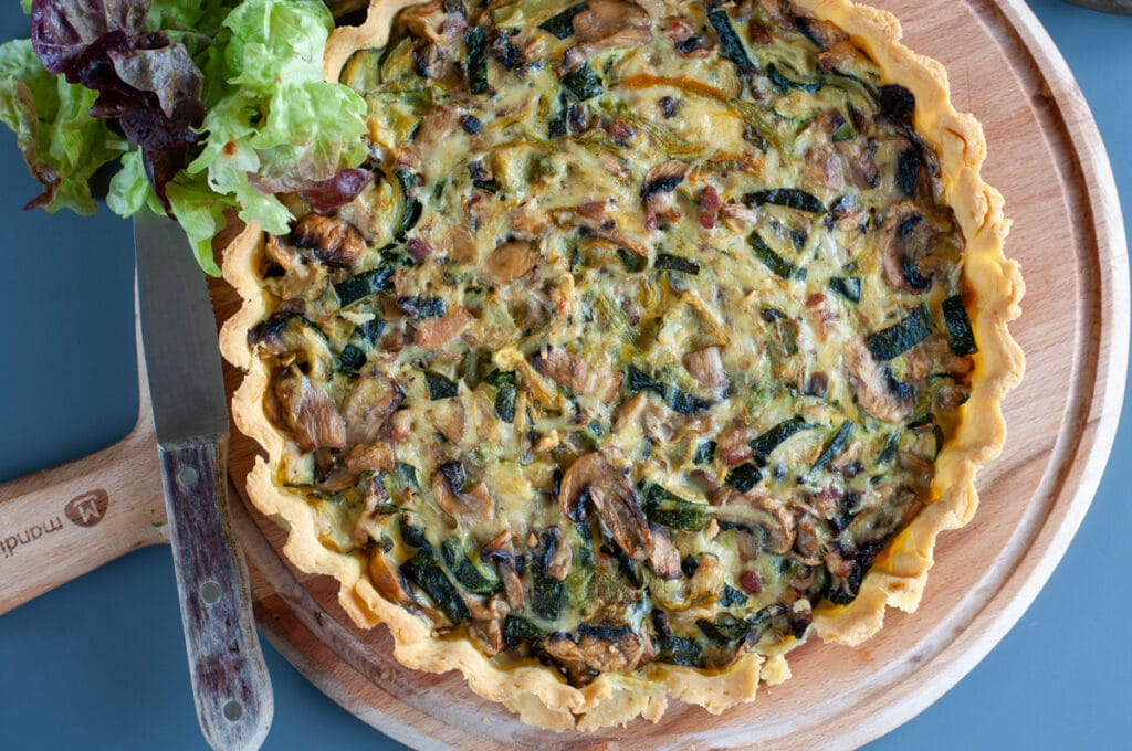 Zucchini mushroom quiche on a cutting board seen from the top